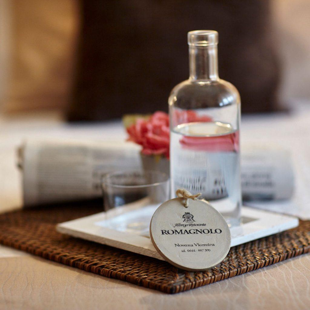 Camera hotel Da Romagnolo con bottiglia d'acqua e giornale