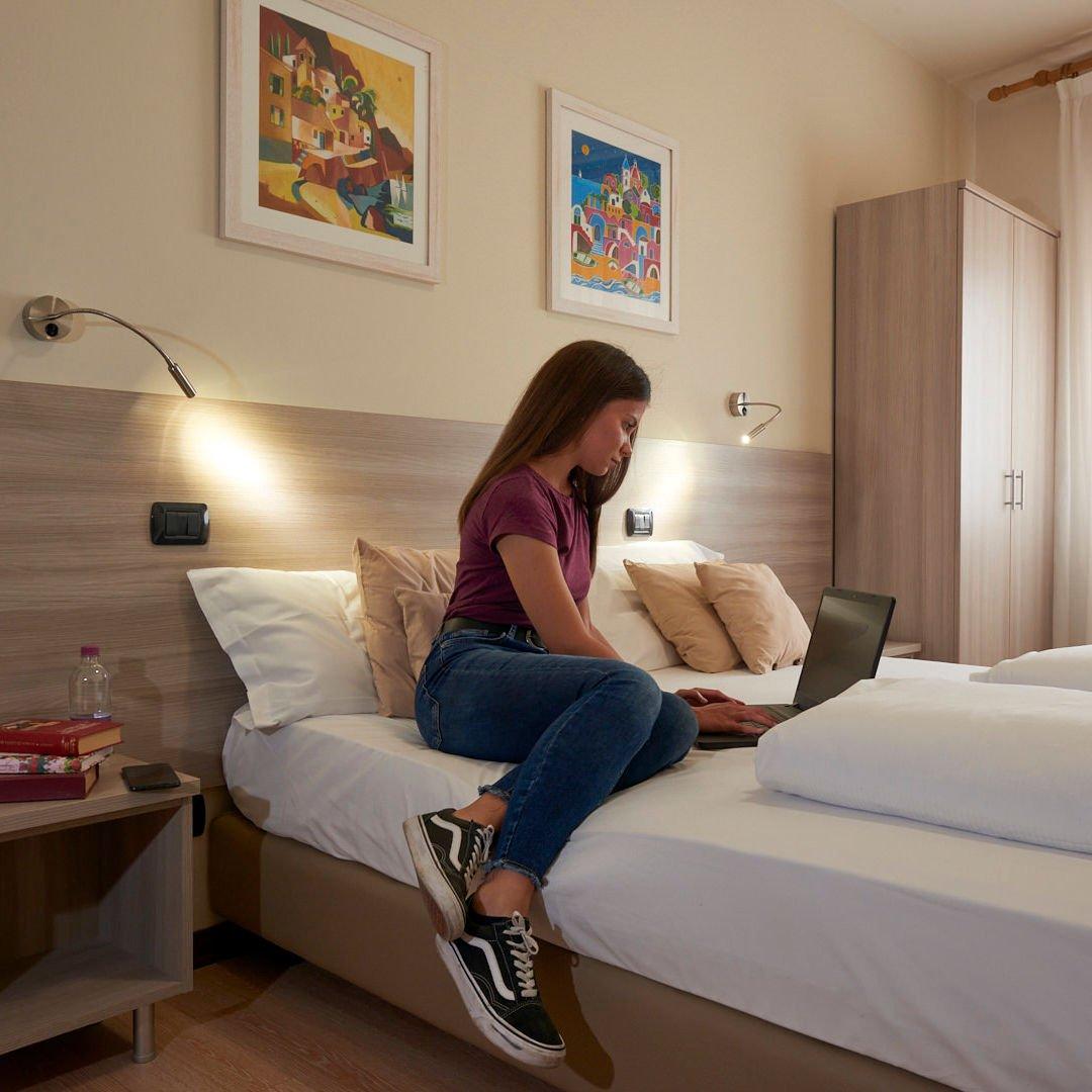 Ospite dell'hotel Da Romagnolo al computer sopra il letto