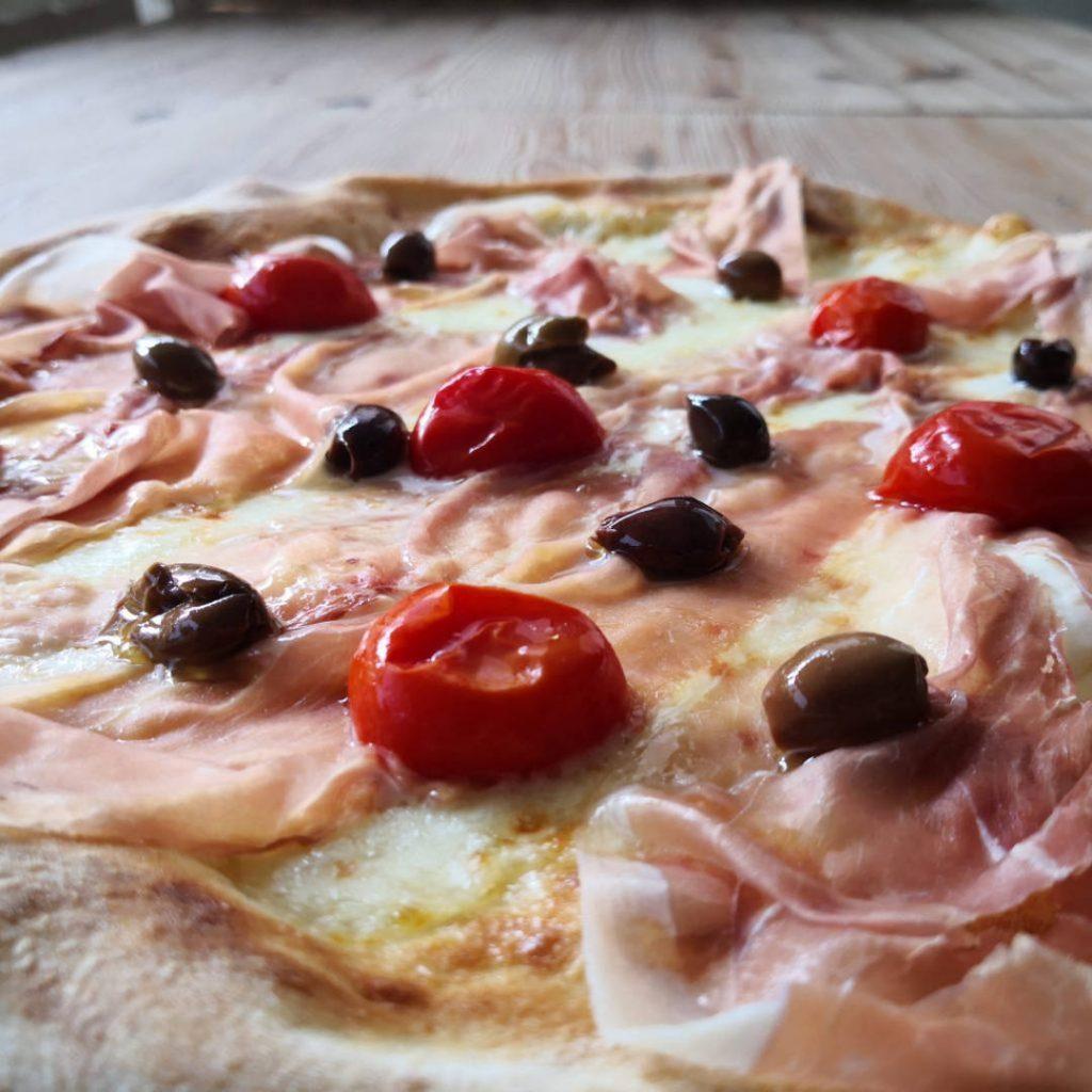 Pizza bianca bufala, olive taggiasche, prosciutto crudo Berico-Euganeo DOP, pomodorini confit